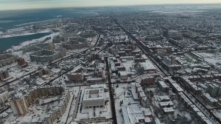 Winter city in the snow with a bird's eye view. Drone removes from a height the provincial city of Cherkasy in Ukraine. Evening, clouds, a lot of snow, architectural buildings. #1025378774