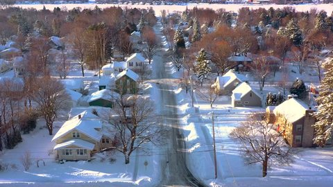 Peaceful small town under deep, fresh snow, early morning in Winter, aerial view.