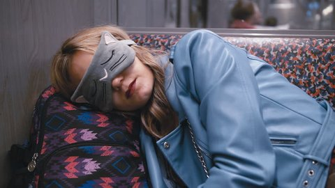 Slow Motion Young beautiful girl in the Blindfold on the eyes, fell asleep on the subway train. Head put on a backpack. CloseUp.