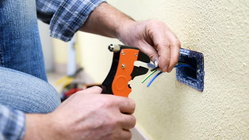 Electrician technician worker with wire stripper plier prepares the electric cable in a residential electrical system. Construction industry. Building. Footage.