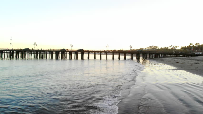 Aerial drone shot low over the water surface of the Pacific Ocean beach at sunset off the coast of Santa Barbara with Stearns Wharf pier in California.