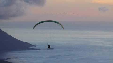 Hang glider navigates his way across the sky during sunset with coastline in background
