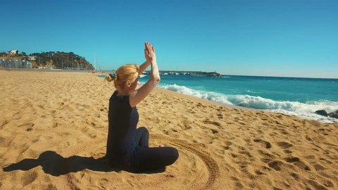 Young woman meditating in lotus pose on sea beach. Sporty girl practicing yoga outdoors at sunny day. Woman in yoga asana relaxation at tropical beach. Summer vacation in Spain