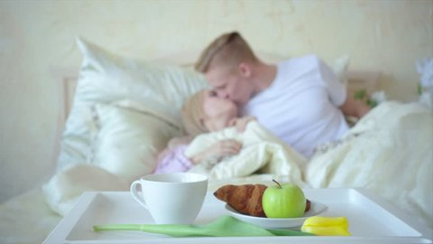 Breakfast in bed, couple on the background out of focus