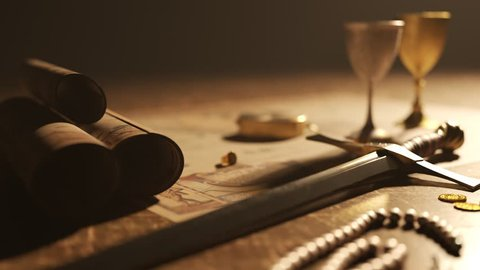Close-up on the wooden table with sword, silver and gold goblets and jewels. The vintage compass lying on the ancient map. Instrument was used in sailing at the age of great geographical discoveries.