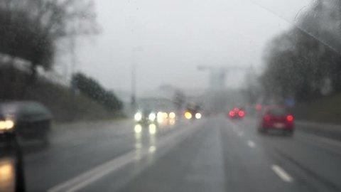 Peering out the windscreen of a car driving through city traffic on a cold rainy afternoon at dusk through mist with windscreen wipers on and car tail lights blur