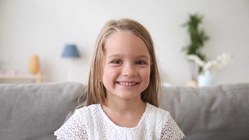 Funny little girl smiling looking at camera at home, cute kid talking to webcam making online video call or recording vlog having fun, preschool child with pretty face waving hand sitting on sofa | Shutterstock HD Video #1025576954