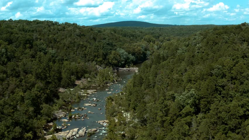 Aerial View of Flowing River, Stream or Creek with rock dam, water rapids, rock formations, green shores and trees