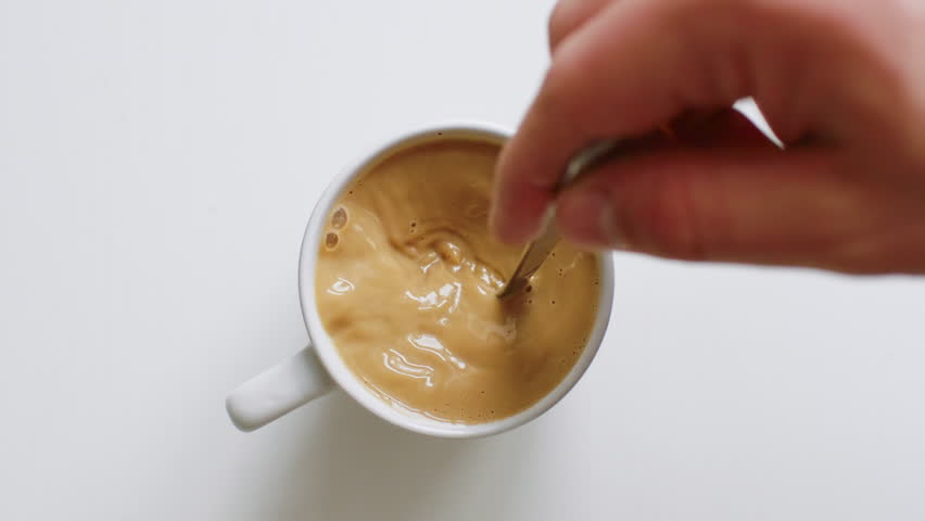 Top view of person hand stirring coffee with spoon #1025627474
