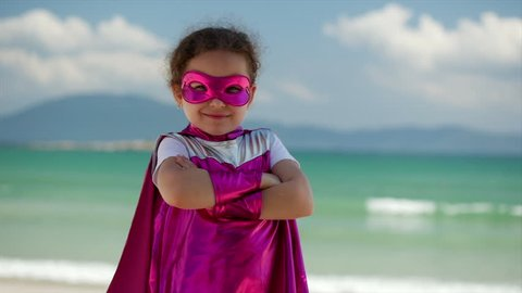Beautiful Little Girl in the Superhero Costume, Dressed in a Pink Cloak and the Mask of the Hero. Plays on the Background Sea and Blue Sky and Clouds, Sends a Fist Forward. Concept of a Happy