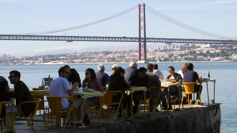 Lisbon, Portugal - March 2nd, 2019: People relax in outdoor restaurant terrace overlooking the iconic 25 April bridge in Lisbon, Portugal
