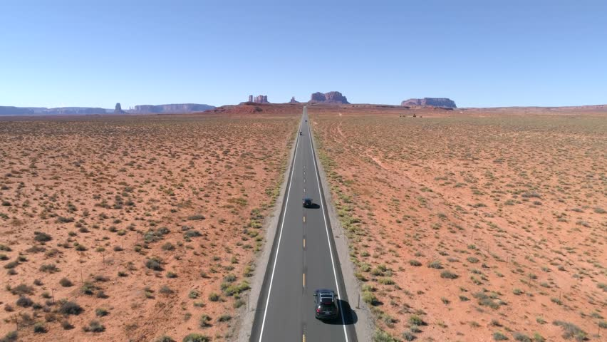 Scenic Byway 163 travels northeast through the Monument Valley. Aerial 4K shot of the redrock desert and spires of scenic landscape. | Shutterstock HD Video #1025651474