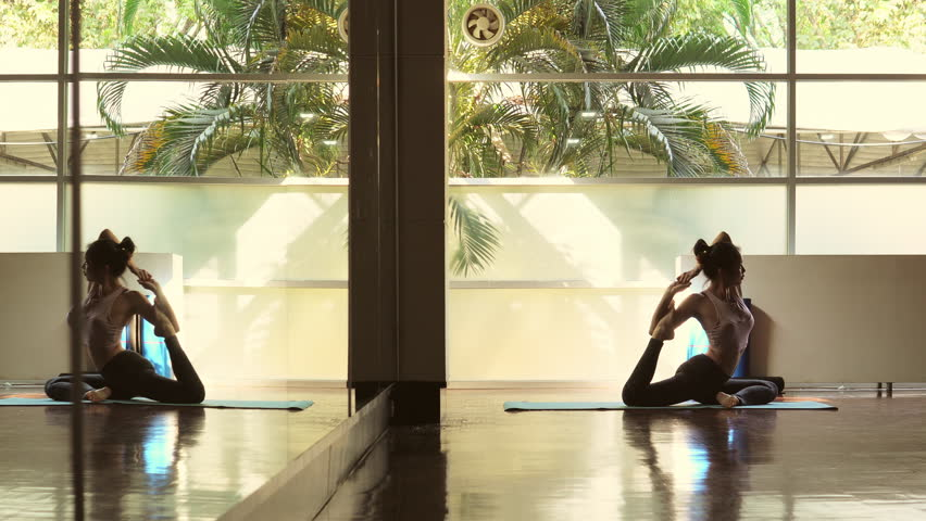 Young beautiful asian woman practising yoga perform one legged king pigeon pose | Shutterstock HD Video #1025687324