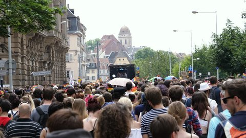 STRASBOURG, FRANCE - CIRCA 2018: People walking following gay truck crowd people waving rainbow flags at annual FestiGays pride gays and lesbians parade marching French streets fun party atmosphere
