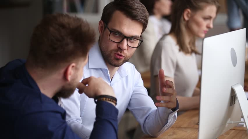 Two male colleagues employees cooperating in office talking working together at workplace, smiling businessmen coworkers discussing planning computer business project brainstorm in corporate teamwork | Shutterstock HD Video #1025732684