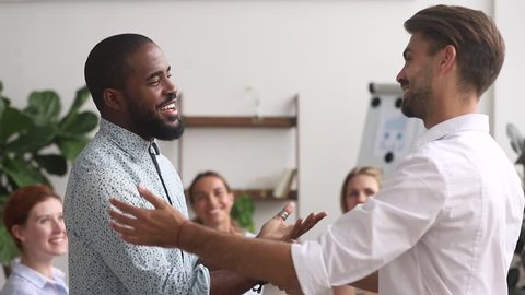 Happy proud excited african american male employee get rewarded appreciated promoted by executive boss manager motivating shaking hand of successful black office worker as gratitude respect concept