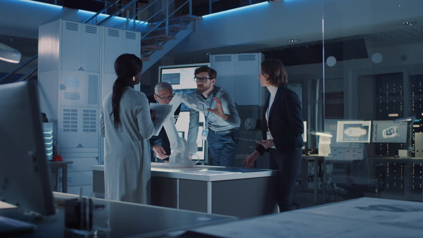 Engineers Meeting in Robotic Research Laboratory: Engineers, Scientists and Developers Gathered Around Illuminated Conference Table, Talking, Using Tablet and Analysing Design of Industrial Robot Arm | Shutterstock HD Video #1025767424