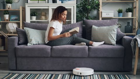 Good-looking African American student is turning on robotic hoover and reading book enjoying hobby and relaxing on couch while gadget is cleaning floor.