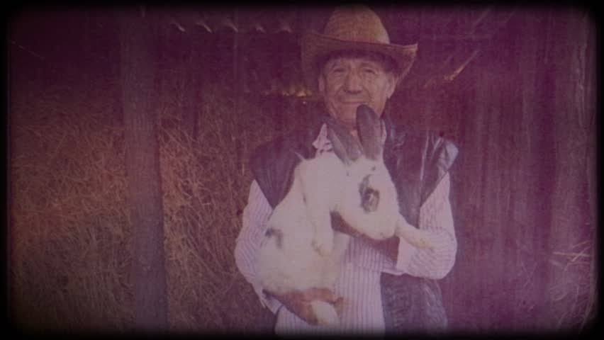 A farmer in a straw hat holds a rabbit in his hands. Farm animals. Raising animals for meat. Portrait of an elderly farmer. Agriculture. Organic food. Ranch. Not vegetarianism, but meat-eating | Shutterstock HD Video #1025818424