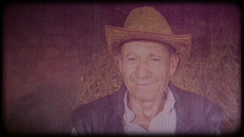 Old farmer in a straw hat near the farm. Portrait of an elderly man. Retiree. Video archive. Retro. Vintage. Farm animals. Raising animals for meat. Agriculture. Organic food. Ranch | Shutterstock HD Video #1025821784