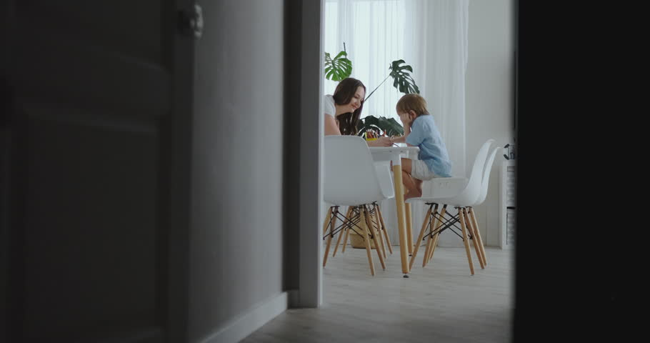 Mom helps sons learn to draw doing homework preschool preparation at home sitting in the white kitchen. Two brothers draw a portrait of mom together | Shutterstock HD Video #1025823974