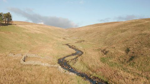 Aerial landscape video flying over meandering river or steam in remote valley, Kingsdale, Yorkshire Dales, England, Uk