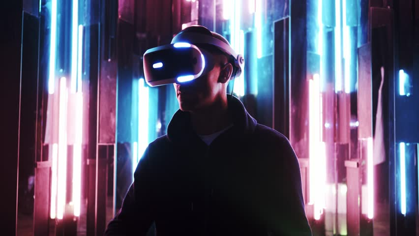 Faceless man wearing VR headset in dark space with neon light lamps, user moving hands, scrolling virtual pages, shooting through colored flares and bokeh on foreground | Shutterstock HD Video #1025833244