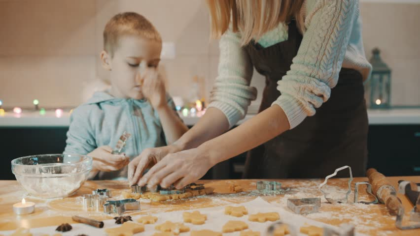 Happy mother and son baking Christmas cookies in the kitchen. Family life before the holidays at home. | Shutterstock HD Video #1025843294