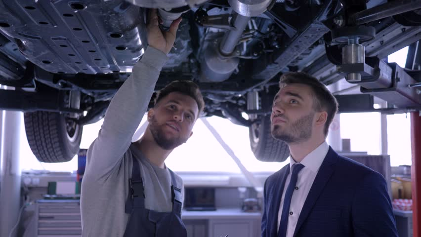 auto mechanic inspections technical condition vehicle on mechanical lift with male client in car service then happy men shake hands and look at camera #1025846234