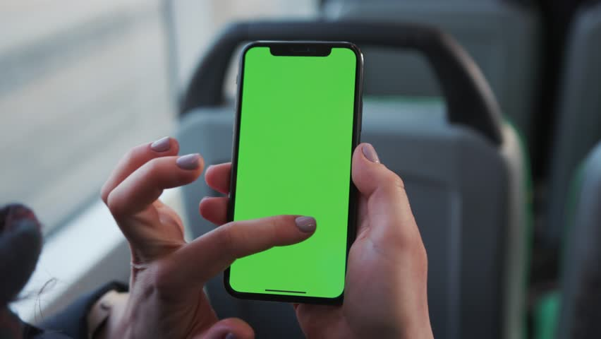 Lviv, Ukraine - May 19, 2018: Closeup of a woman's hand holding a mobile telephone with a vertical green screen in tram chroma key smartphone technology cell phone street touch message display hand | Shutterstock HD Video #1025899454