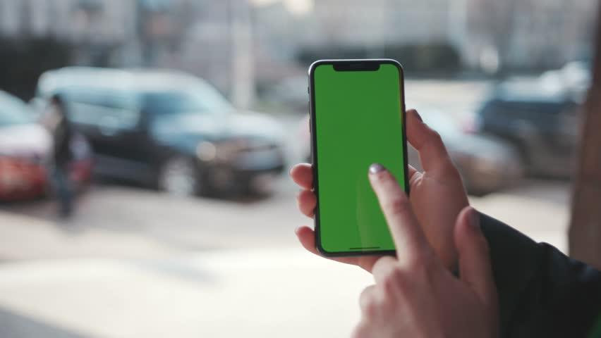 Lviv, Ukraine - May 19, 2018: Slow motion shot of woman hands holding phone with horizontal green screen on city street background sunset people car busy finger touch message cellphone display girl | Shutterstock HD Video #1025899484