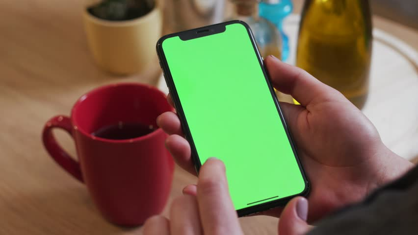 Tokio, Japan - April 7, 2018: Woman hand hold use touch phone with vertical green screen on kitchen at home drink tea breakfast browse food girl house shop healthy internet abstract slow motion | Shutterstock HD Video #1025899514