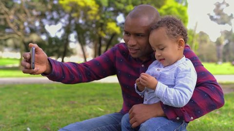 African-american young bald father in striped shirt and jeans sitting on haunches in park, holding his little mixed-race son on knees, making selfie. Side view. Family, holiday concept