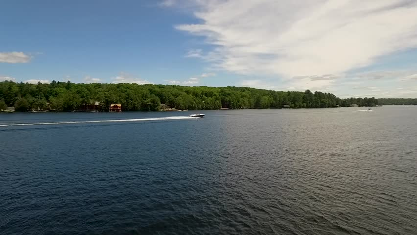A boat travels across a calm lake on a sunny day. | Shutterstock HD Video #1025928794