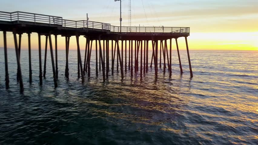 Spectacular aerial drone view of the pier in-between the low tide waves, isolated against the sunset across the horizon in Pismo Beach, California | Shutterstock HD Video #1025941394