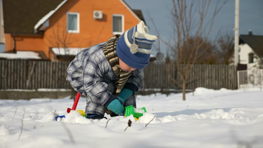 Little Boy Plays With Toy Trucks on Snow in Backyard Garden. Cold Weather on Winter Holidays. Bright Sunny Day. Slow motion 0.5 speed 60 fps | Shutterstock HD Video #1025946944