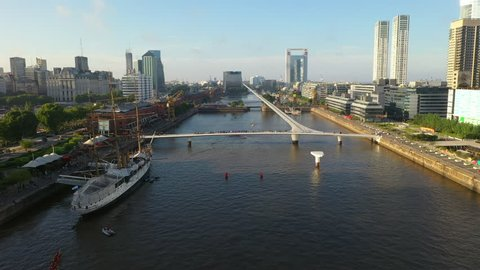 Aerial drone view of Puerto Madero harbor with Puente de la Mujer bridge and skyscraper buildings in the background. Buenos Aires, Argentina.