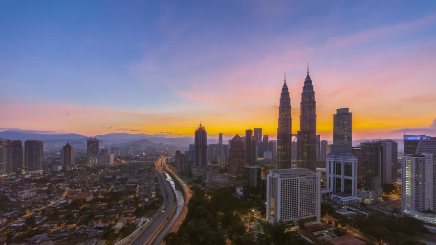 Aerial time lapse view of a city skyline with busy streets and expressway of  Malaysia at sunrise from twilight to day.  | Shutterstock HD Video #1025955104