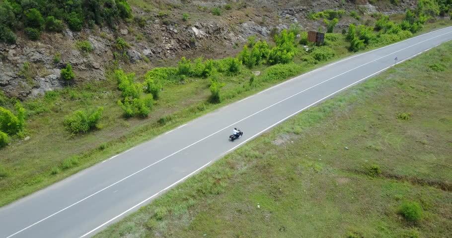 Drone camera following a biker in a highway | Shutterstock HD Video #1025963984