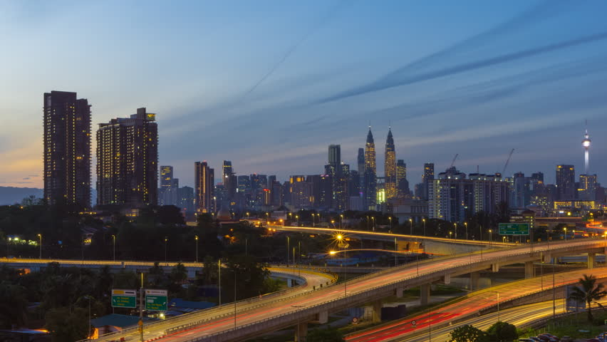 Time Lapse: Aerial view overlooking busy layers of elevated expressway at sunrise with a city skyline in the background in Malaysia. | Shutterstock HD Video #1025974904