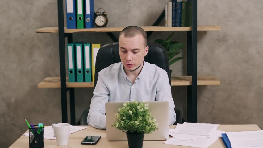 Young man doing paperwork in office | Shutterstock HD Video #1025974994