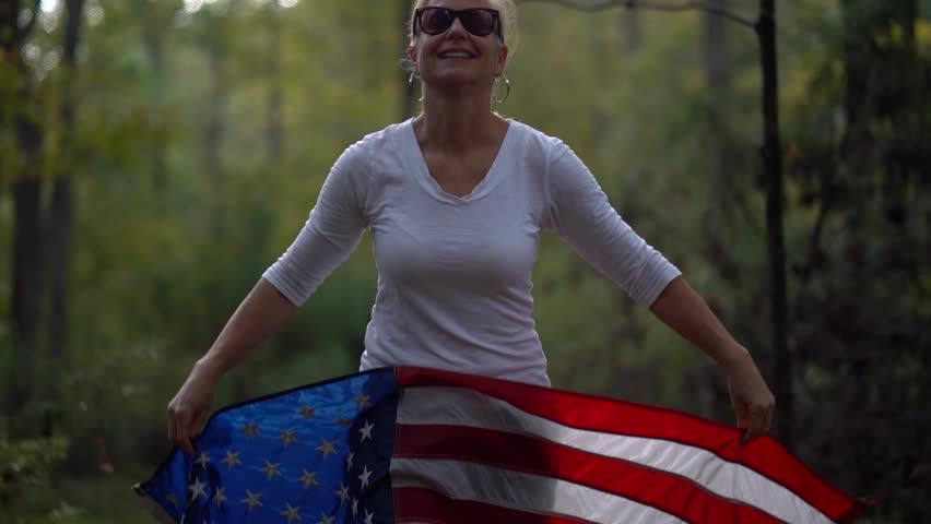 Pretty, mature woman wearing sunglasses and smiling pulls an American flag up over her head and them back again in slow motion.