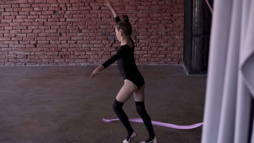 Rhythmic gymnastics: Girl in black body perform gymnastics exercise with a pink ribbon in studio with windows and brick wall background at gymnastics school. Workout, slow motion #1025983664