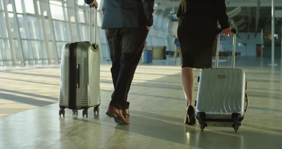 Back view on the Caucasian businessman and businesswoman walking the airport hall and carrying their suitcases on the wheels before the departure to the working trip. Rear. Camera moving from feet up. | Shutterstock HD Video #1026000554