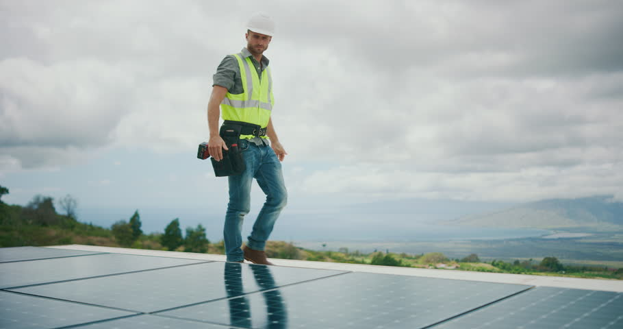 Sustainable green energy jobs, solar panel technician surveying solar panels #1026077894