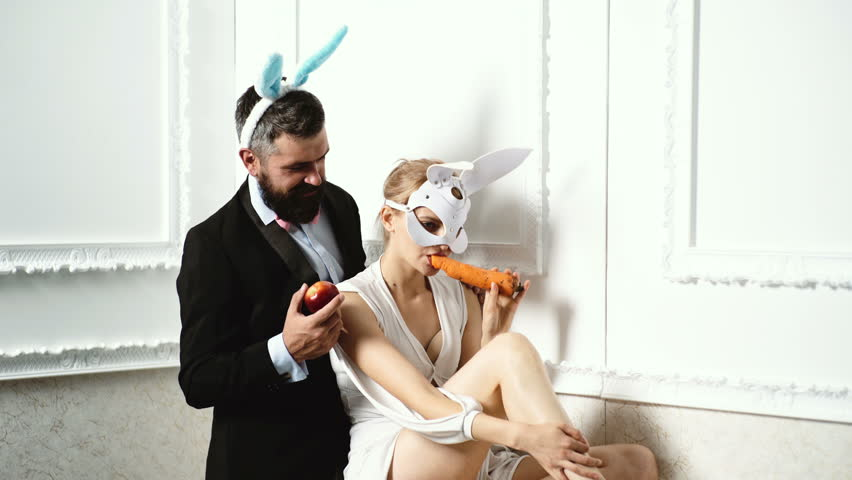 Surprised bunny couple wearing bunny ears and eat carrot. Bunny rabbit ears costume. Funny easter bunny. Happy couple preparing for Easter. Easter rabbits