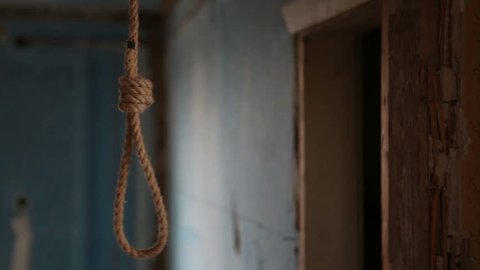 A rope loop for suicide hangs in a wooden hut. Suicide in an abandoned house.