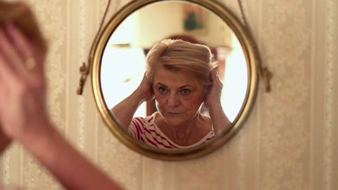 Beautiful, sad senior woman checking her look in front of the mirror, slow motion