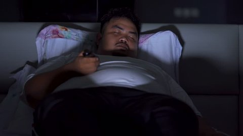 Young obese man sleeping on the bed at night after watching TV while holding the remote control. Shot in 4k resolution