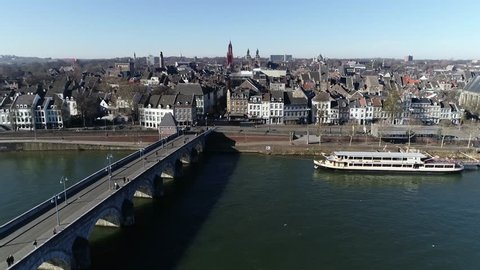 Low altitude aerial view of Sint Servaasbrug is an arched stone footbridge across the Meuse River in Maastricht Netherlands and the oldest bridge in Holland also showing cityscape in background 4k